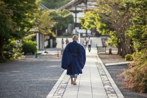 お寺の中を歩いている仏教僧侶の後ろ姿