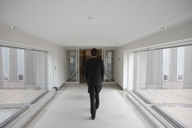 火葬場の廊下を柩を押しながら歩いている葬祭ディレクターの男性。
