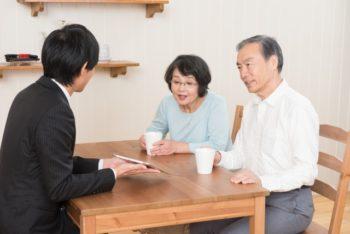 老夫婦が葬儀の事前相談と見積もりの説明を受けている様子