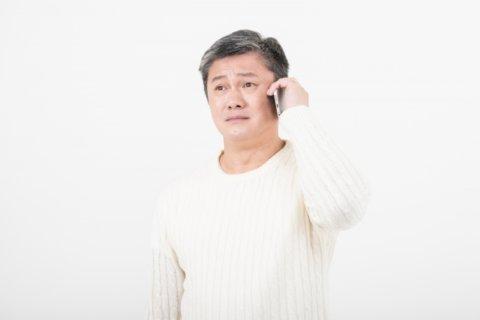 悲しい表情で電話をしている男性。