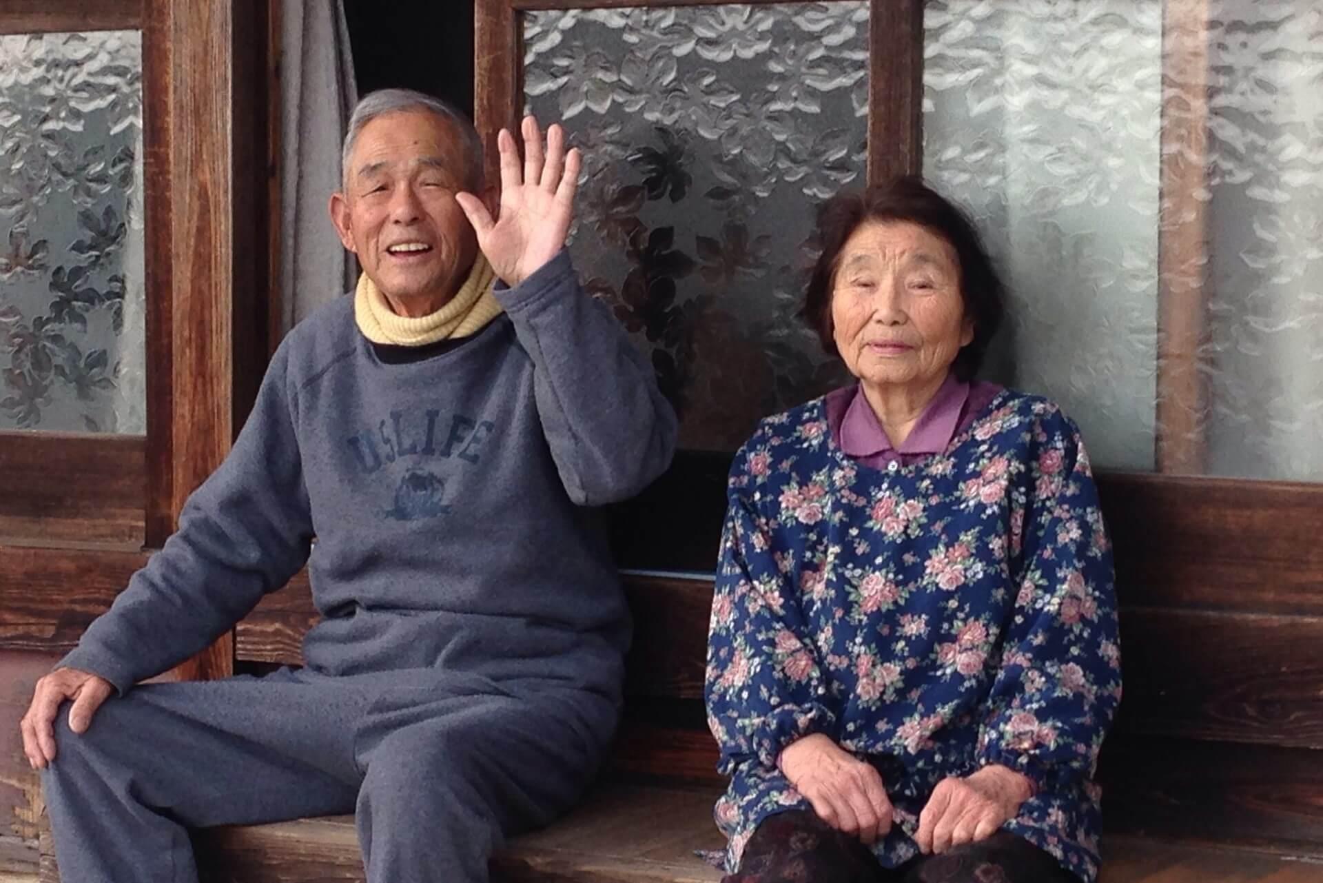 ベンチに腰掛けてこちらに手を振っている老夫婦