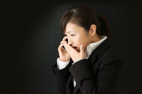 電話を受け驚いて動揺している女性。