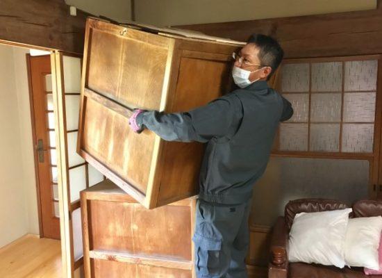 遺品整理の大きな箱を運んでいる男性。