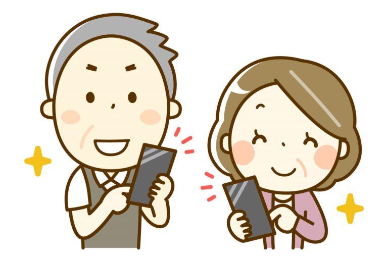 スマートフォンを手に取り微笑んでいる老夫婦。
