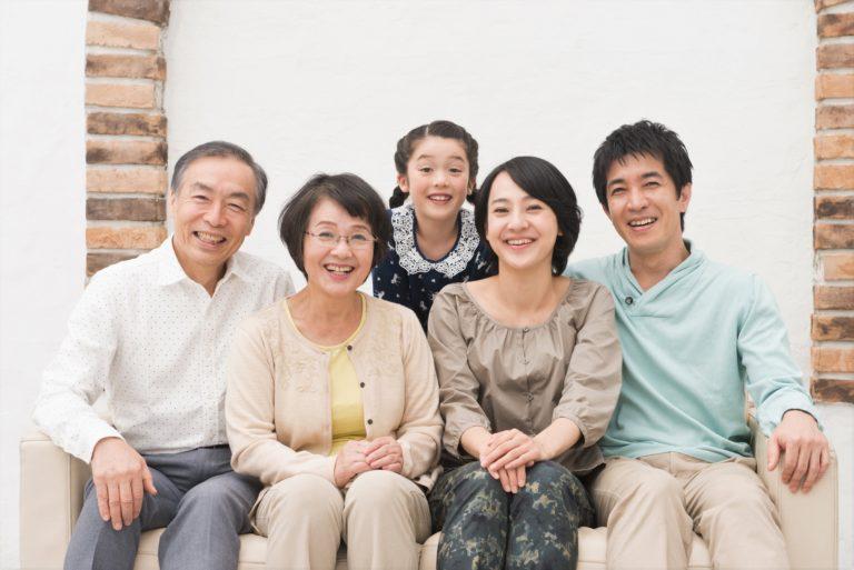 こちらに微笑みかけている三世代家族