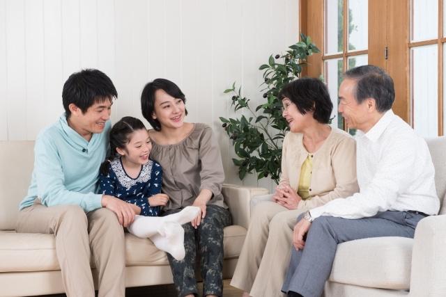 ソファに座りながら歓談している3世代家族