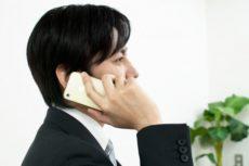 スマートフォンで手配先へ電話をしている男性
