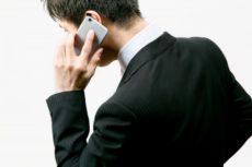 スマートフォンで手配の電話をしているスーツ姿の男性