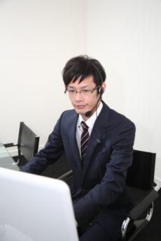 パソコン画面を確認しながら電話応対をしている男性のオペレーター