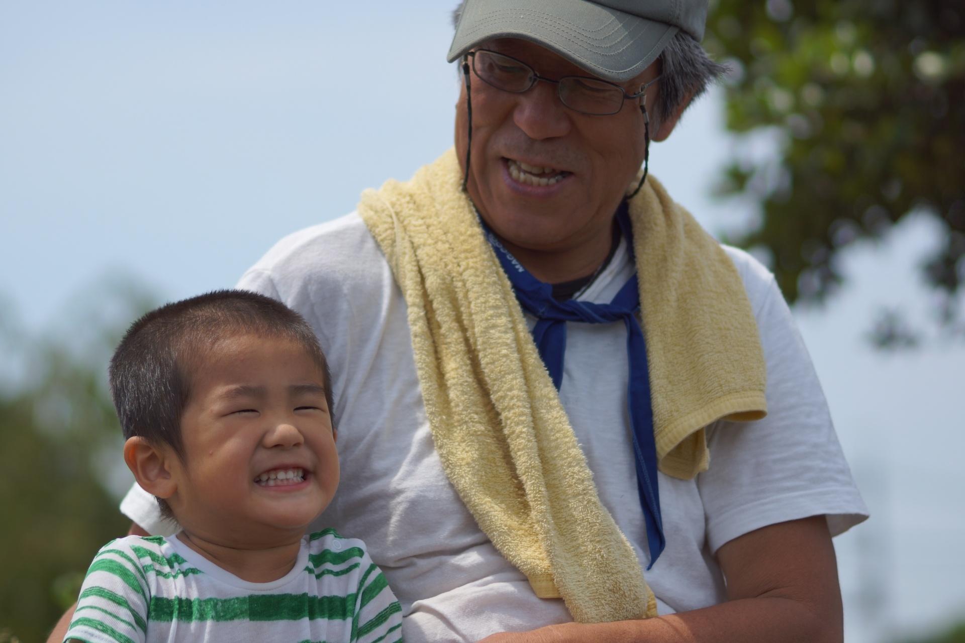 笑っている孫とそれを見て微笑んでいる老人。