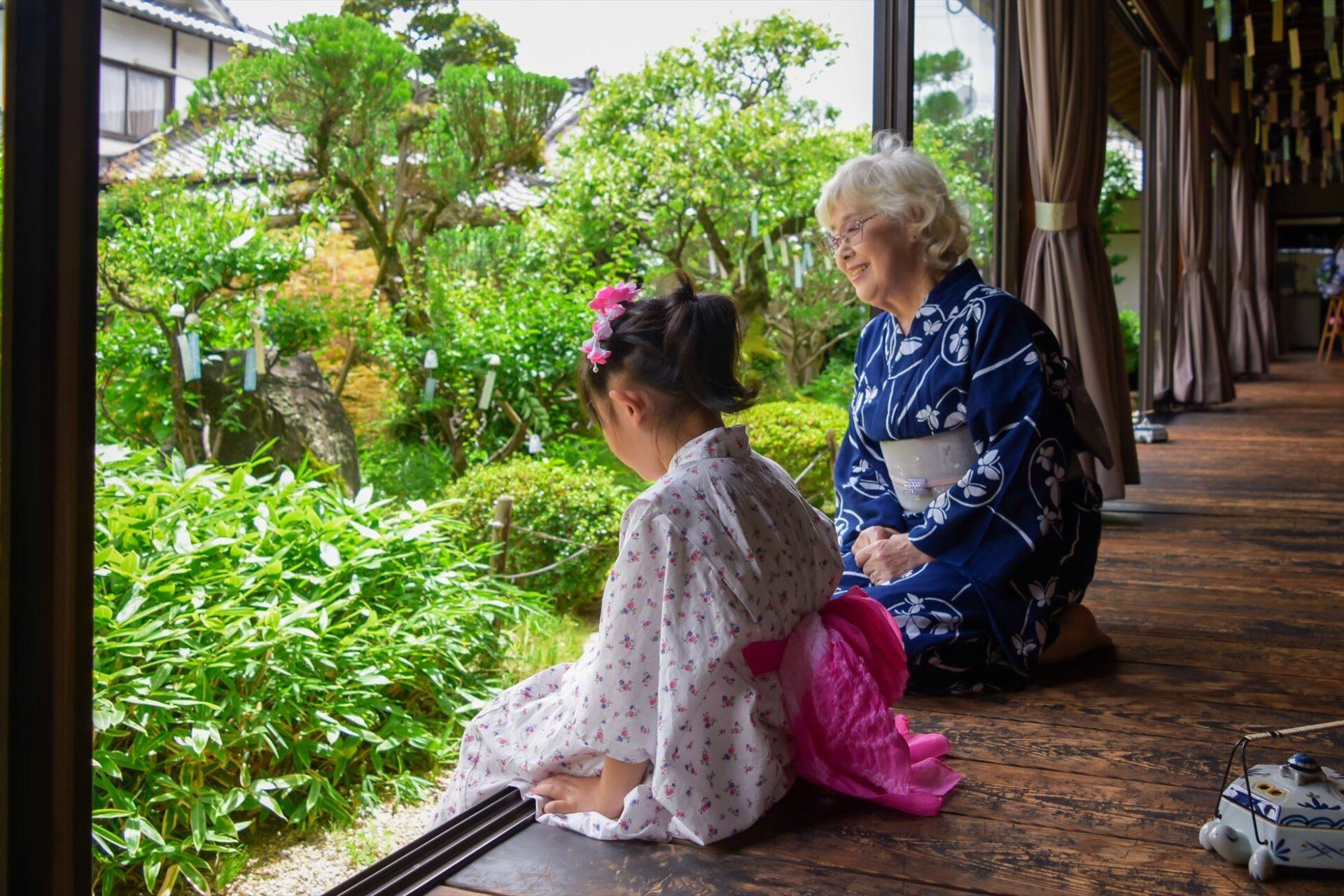 ベンチに座っている和服姿の老女とその孫娘。